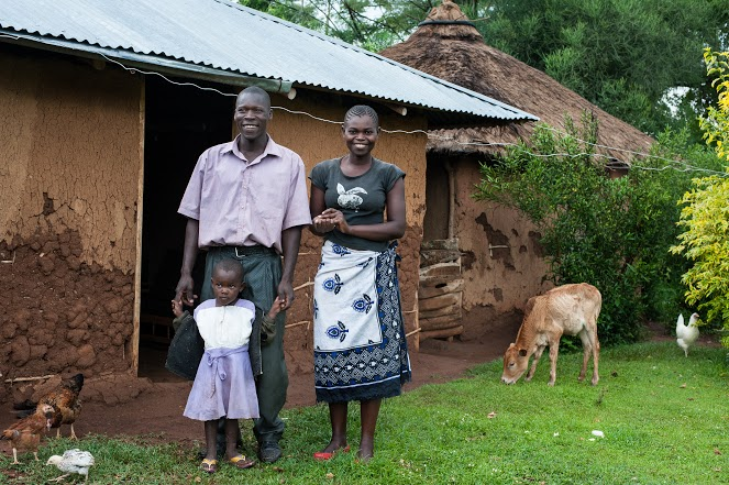 At the home of recipient Gabriel Otieno Awoche in Koga village on 22 October 2014. Gabriel built a house and chicken coop with the cash. He also bought woodworking tools for his furniture workshop. Gabriel with his wife Lucy Adhiambo and their daughter Charlotte, 3. They also have another daughter, Mariam, age 1 1/2.