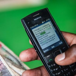 Senior Field Officer Mike Otieno withdraws cash at an Mpesa kiosk in Kogelo on 23 October 2014
